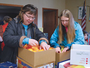 Gayle and Catherine Bechen look through their fruit to make sure everything is okay.