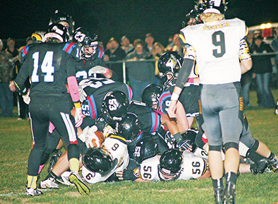 Blackhawks pile-up on the Warbirds runner, hoping to cause a fumble after taking him down during Friday night's battle in Woonsocket.