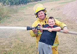 Chance Machado enjoying squirting the fire hose with volunteer firefighter Ryan Bechen.