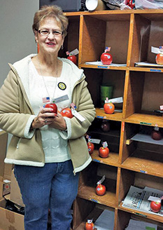 SANDI RUML, president of the Letcher Legion Auxiliary delivered apples to the teachers at Sanborn Central School last Monday in recognition of National Education Week.