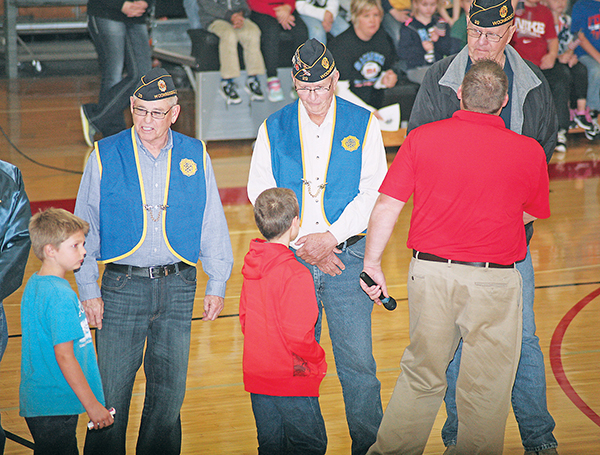 JIM HEGG, Keith Senska and Jerome Anderson, local veterans, shake hands with Supt. Rod Weber and receive gifts from the elementary kids during Wednesday's Veteran's Day Program.