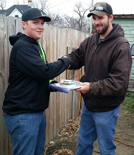 Volunteer fireman Neil Hiemstra receives a plate of Christmas goodies from Evan Ohlrogge.