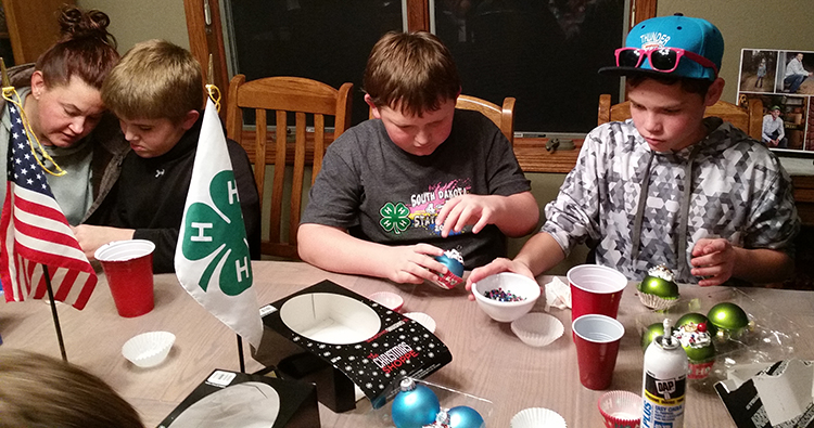 Club members work on their ornaments for the club Christmas tree to be put up in the Courthouse. Pictured left to right are: Club Leader Sarah Olinger, Kade Olinger, Blake Howard and Jordan Wieting.