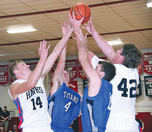 DILLON MOORE and Brady Tiede fight two Titan defenders for a rebound during second quarter action Monday night in Woonsocket.  Moore and Tiede, both seniors, were first and second high point men for the Blackhawks with 21 and 19 points, respectively.