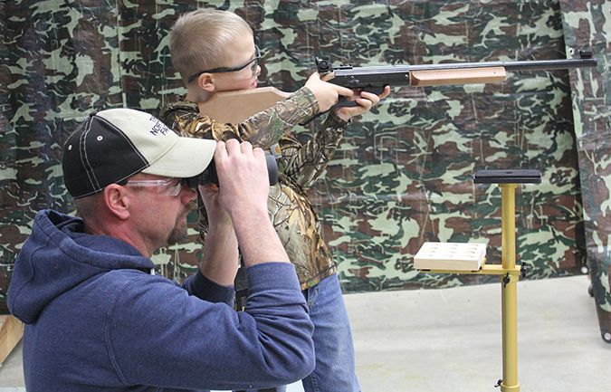 Devyn Brooks shoots a BB gun while his dad, John Brooks, assists him on the line.
