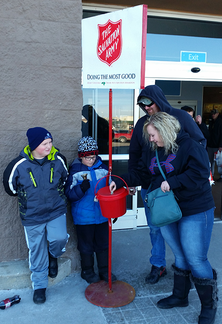 Blake Howard and Carver Lindsey accept a donation for the Salvation Army from Woonsocket locals Garret Foos and JoLynn Kopfmann outside Wal-Mart in Mitchell.