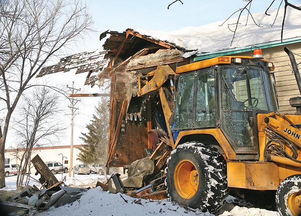 CULLY EVERS of Evers Excavation uses his backhoe to demolish a house near main street in Woonsocket.