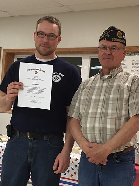 LETCHER VOLUNTEER Fireman Aaron Roth receives the Fireman of the Year award from Legion Commander Ron Ruml.