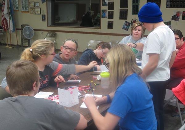 Older members creating Valentine cards to send to community members.
