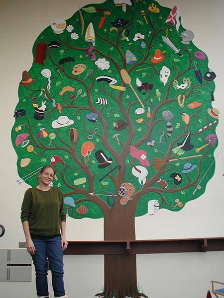 Shaila Huth stands with the beautiful mural she painted at the Pepsi Cola Theatre.