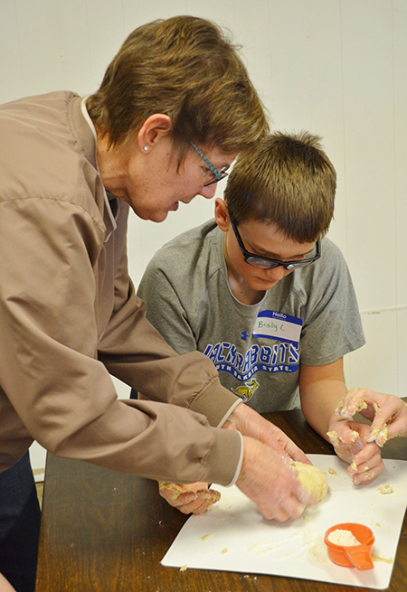 Tina Kieffer, Administrative Assistant from Aurora County, works with Brady Larson as he kneads his bread dough.