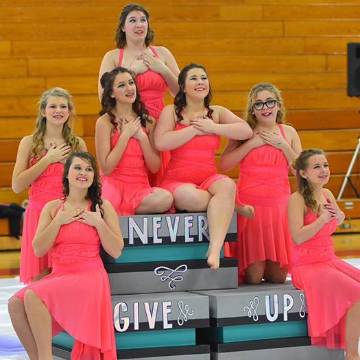 "The Blackhawks Winterguard team finishes their performance with the message ""Never Give Up.""  Pictured clockwise are McKenzy, Megan, Adriana, Renee, Breanne, Josie and Brooklyn."
