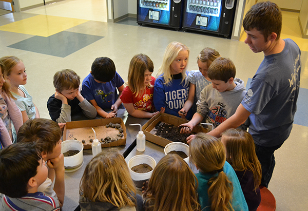 FFA Member Aaron Linke teaches elementary students about evaluating and judging soils, a fall CDE event.
