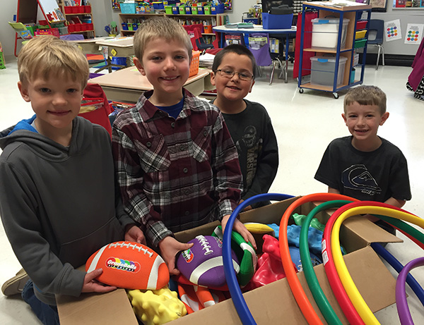 Carter Edwards, Mason Kempf, Ian Octavo and Layton Zoss check out the box of items from DonorsChoose.org.