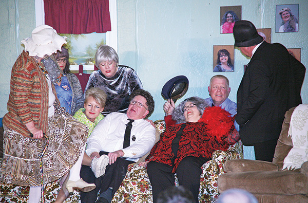 "THE SPINSTER women who are left after two deadly tea parties, played by Margie Larson, Anita Fouberg, Lisa Snedeker and Carrie Howard, fawn over their shared love obsession, ""Dennis O'Finn"" (Gayle Feistner), while Detectives ""Kramer"" (Tom Fouberg) and ""Wing"" (Jack Davis) prepare to take a selfie with the deceased, Carrie ""Nettie Norton"" Gutierrez."