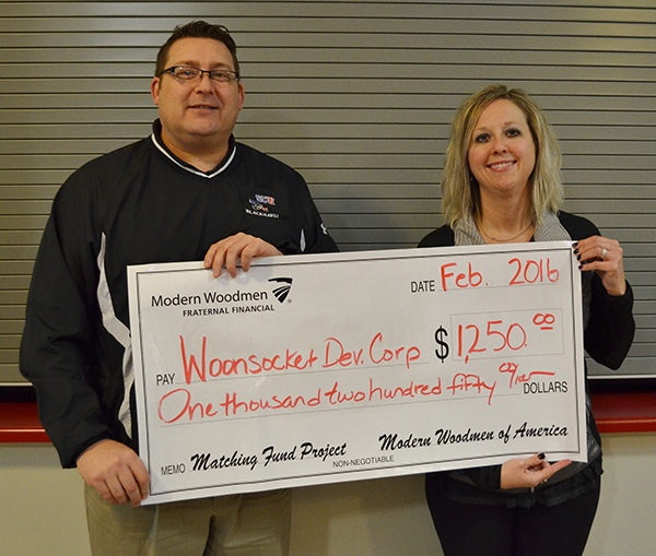 Modern Woodmen Representative Stacey Malde presents Rod Weber with a $1,250 check for matching funds from their Family Fun Day fundraiser to raise money for the Woonsocket Community Center Theatre addition.