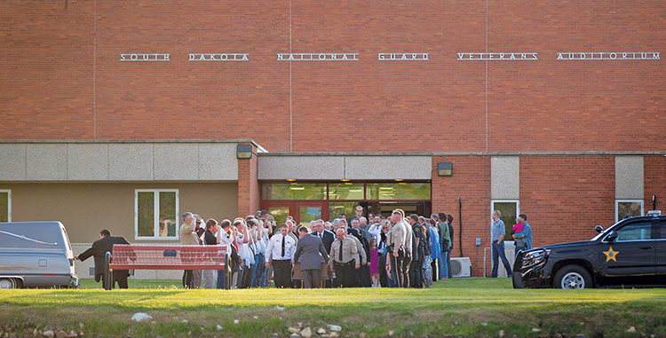 Law enforcement colleagues and local friends show their respect for Anderson and their support for his family as the casket is brought from the gymnasium following services Thursday evening in Woonsocket.