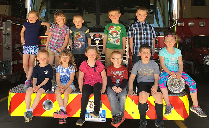 RIGHT: Kindergarten class from Sanborn Central Elementary enjoyed a day at the Mitchell fire station recently, as part of their spring field trip. The class is pictured at right on one of the department's trucks.