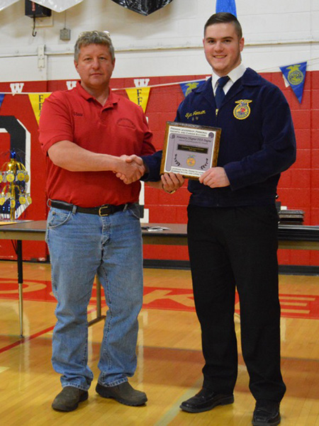 Steve Gaston accepts his Honorary Degree on behalf of Forestburg Farmers Elevator from Tyler Johnson.
