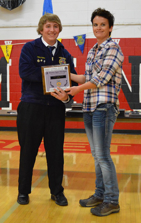Hillary Lutter accepts her Honorary Degree for the Sanborn Weekly Journal from Bailey Schmiedt.