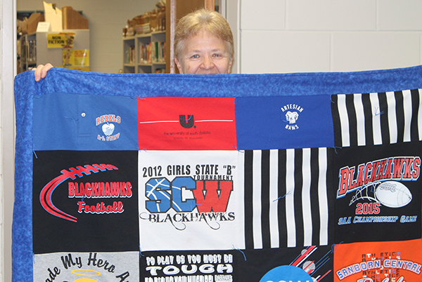 "The staff presented a quilt  to Linda Whitney Tuesday morning at a ""surprise"" breakfast.  The quilt is made of t-shirts from her colleges and Artesian, Artesian-Letcher, and Sanborn Central."