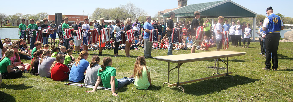 The School flag detail, led by Rex Schlicht, presents unserviceable US flags for disposal during the Legion flag burning ceremony.