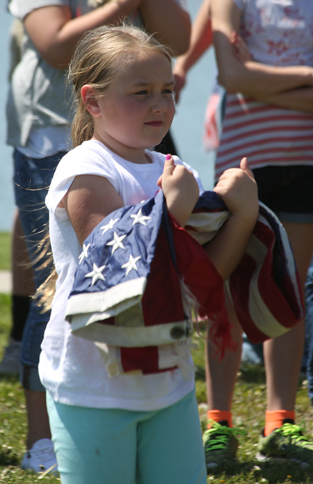 Danielle Brooks brings forward a US flag for disposal during the Legion flag burning ceremony.