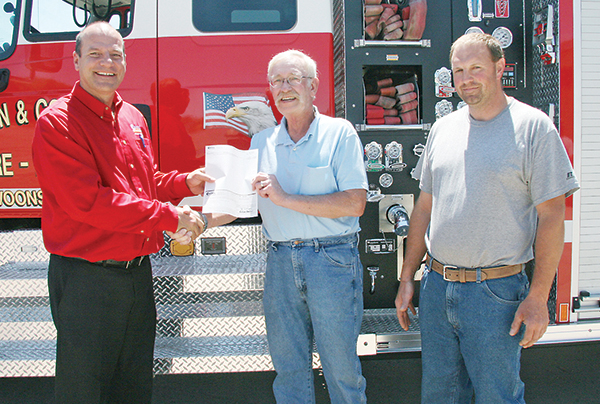 GENERAL MANAGER of Central Electric in Mitchell Ken Schlimgen presents check to Alan Linke, representing the T&C Fire Department, and Fire Chief Travis Coulthard.