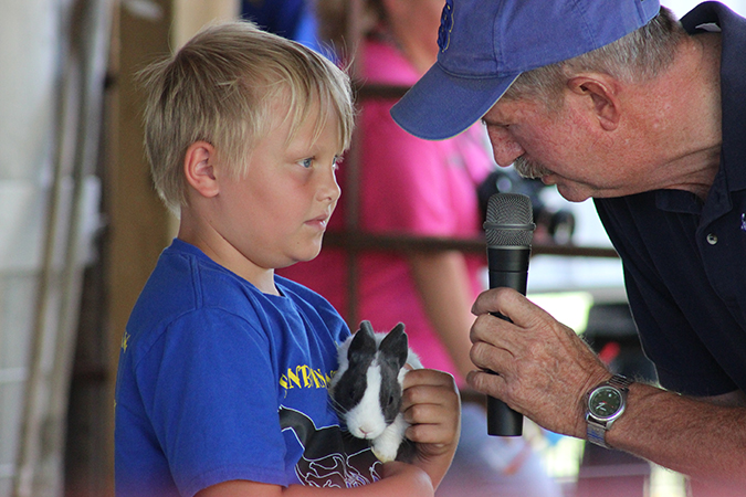 DEVYN BROOKS tells livestock show emcee Jim Johannsen about his rabbit, for which he won the Beginnner Showmanship contest. Devyn is the son of John and Liz Brooks of Woonsocket.