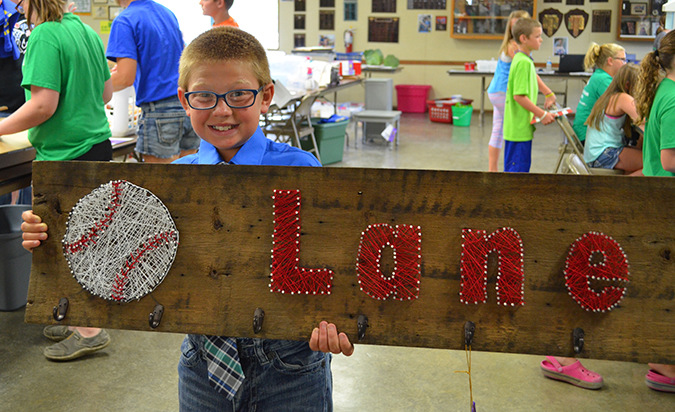 Participating in his first Achievement Days, Lane Burkel proudly shows off his string art sign.