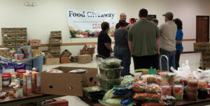 COURTHOUSE EMPLOYEES and volunteers gather for instructions before the distribution of food at the giveaway.