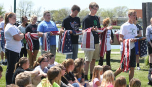 4-H Member Rex Schlicht leads the Woonsocket School participation in a flag burning ceremony he organized between his 4-H Club and the American Legion this past May.