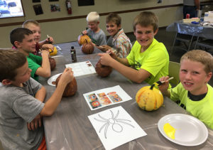 4-H Club members paint pumpkins.