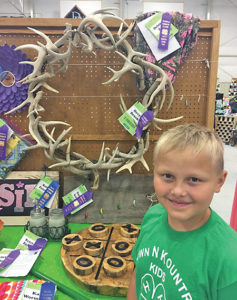 RIGHT: Sanborn County 4-H member Devyn Brooks shows off his purple-ribbon antler wreath that he made as a 4-H project.