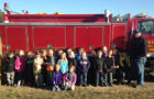 Firefighters from the Artesian Fire Department visited at Sanborn Central School to kick off Fire Prevention Week.    Kasey Bechen and Michael Morgan talked to the students in grades Pre-K through fifth. Ryan Bechen  and Travis King showed the firetruck to the students and allowed them to man the hoses. At right, Artesian volunteer fireman Ryan Bechen helps Carley  Edwards  man a fire hose.