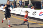 JEFF SCHULZ runs the favorite part of his race, final stretch across the finish line with his son, Jobe, Sunday morning at the Mankato Marathon.