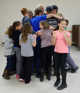 4-H Club members do a group hug during a Character activity on Caring led by Character Officer Shaun Snedeker.
