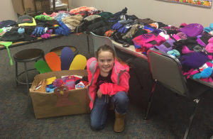 PICTURED IS Hope Baysinger with tables of donated gloves, hats and scarves.