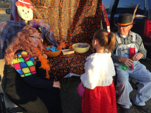 LAMAE AND Lindy Peterson enjoyed passing out treats to kids at last Wednesday evening's trunk or treat at the Lutheran-Methodist church parking lot.