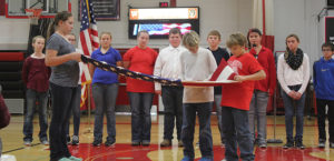 The sixth grade class demonstrates the proper way to fold an American flag with the meaning of each fold.