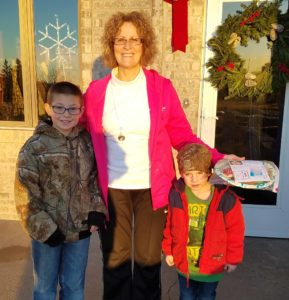 Lane and Ty Burkel deliver a Christmas goodie plate to Nurse Marla Feistner.