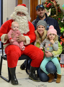 NeAl and Karisa Hiemstra of Woonsocket smile for a photo with Santa, as their children, Hasten and Kapri, think about their Christmas wishes.
