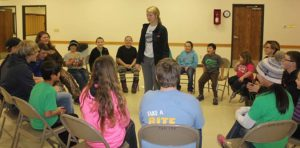"""4-H members wait to hear which group will be called to race to an open seat during a game of """"Valentine Upset""""."""