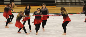 """The Winterguard team performs their """"Insideous Desires"""" routine, using dance moves, props and expressions to express the meaning of the song during competition on Feb. 11. Pictured are Destiny Moe, Jasmine White, Brooklyn Swenson, Adriana Salas, Breanne Brandenburg, Renee Farmer, Josie Weber and Juliet Yeoman."""