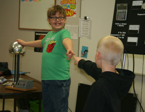 Bryce Larson and Randy Bitterman utilize the generator and static electricity to show how electricity will use the human body as a conductor.