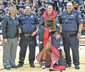 """MYAH SELLAND receives the """"Spirit of Su"""" quilt and plaque from representatives of South Dakota Peace Officers Auxiliary during halftime of the championship game. Myah's older sister, Shelby, also received the honor during the Blackhawks 2014 state title bid. PHOTO COURTESY SOUTH DAKOTA PUBLIC BROADCASTING"""
