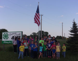 TOWN 'N Kountry 4-H Blue Group members stand in front of  the new flag pole and flag purchased by the club and installed at the meeting.