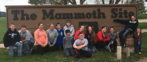 THE WOONSOCKET sixth grade class poses for a picture in front of Hot Spring's Mammoth Site sign.